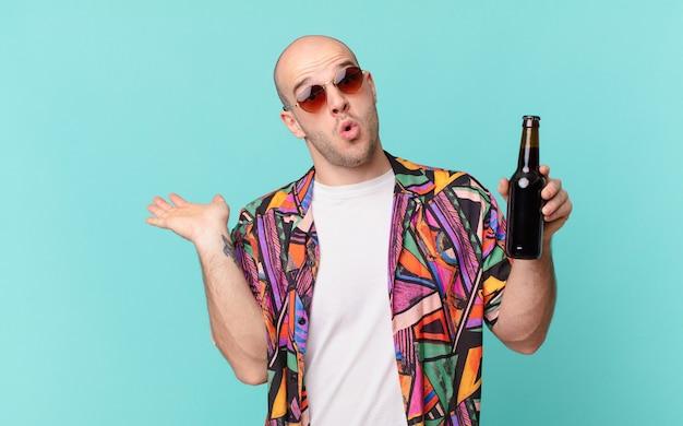 Turista com o homem do turista de cerveja parecendo surpreso e chocado, com o queixo caído segurando um objeto com a mão aberta na lateral