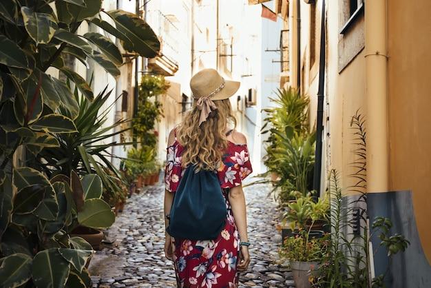 Turista com um vestido floral vermelho, caminhando por um beco cercado de prédios durante o dia