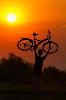 Turista com uma bicicleta no fundo por do sol.