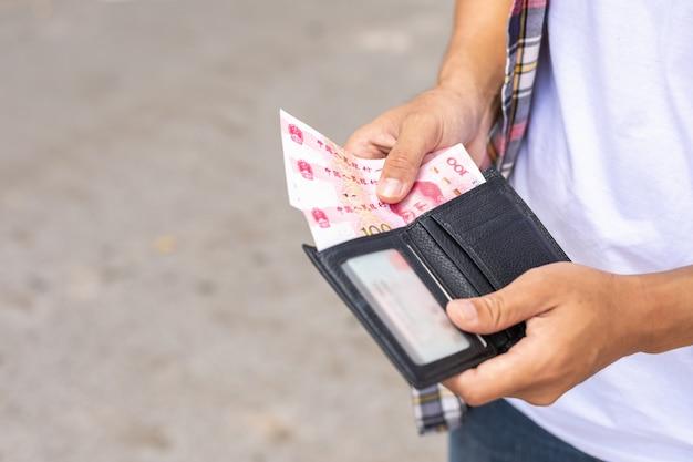 Turista contando ou verificando notas na carteira preta que ele encontrou na atração turística
