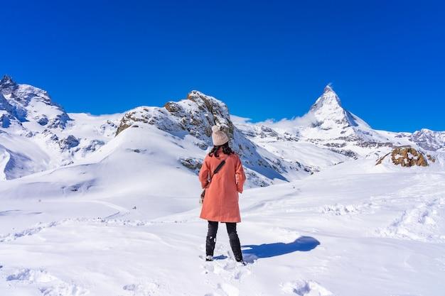Turista da jovem mulher que aprecia com pico de matterhorn da montanha da neve no dia de inverno, zermatt, suíça.