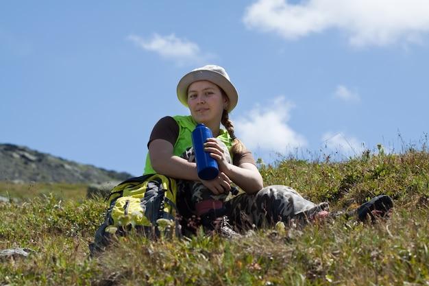 Turista das montanhas que bebe da garrafa