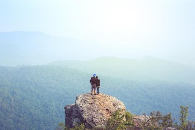 Turista de ásia do homem novo na montanha está olhando sobre o nascer do sol da manhã enevoada e nevoenta