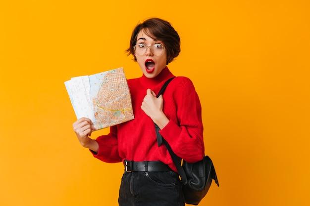 Turista de cabelo curto chocado em pé na parede amarela