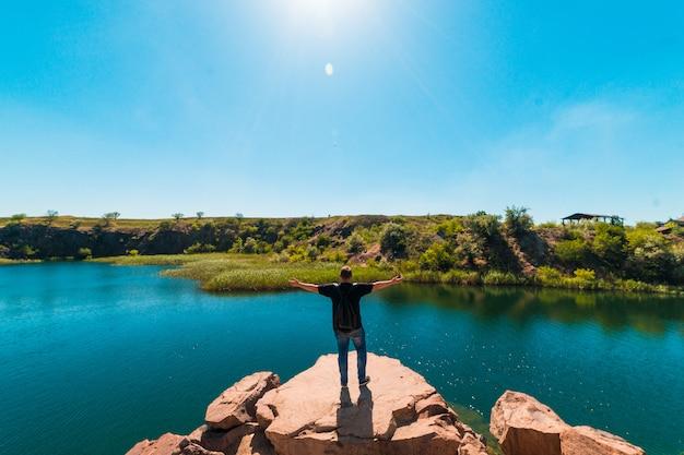 Turista de cara em um penhasco, olhando para uma lagoa, turismo, férias, viagens, férias de verão