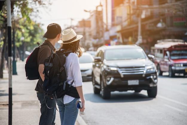 Turista de casal asiático a atravessar a estrada