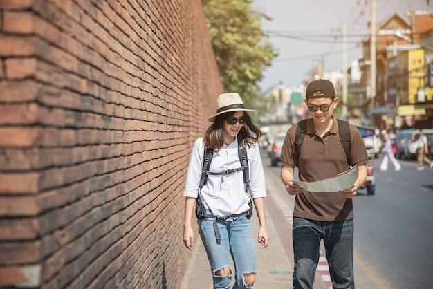 Turista de casal asiático segurando o mapa da cidade atravessando a estrada