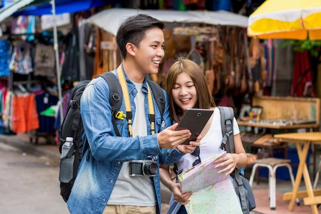 Turista de casal asiático usando tablet para encontrar localização enquanto viaja em bangkok