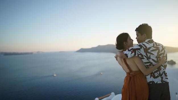 Turista de casal visitando a vila caiada de branco em oia, santorini, grécia. mar mediterrâneo.