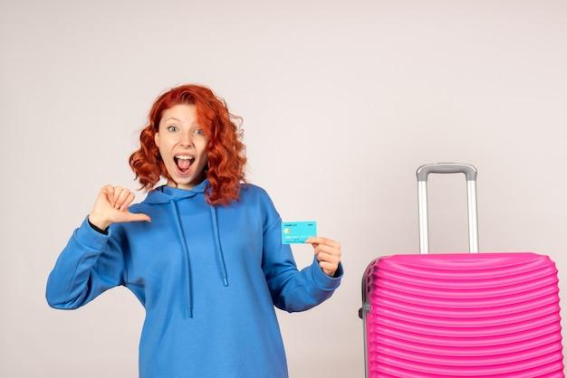 Turista de frente com bolsa rosa e cartão do banco