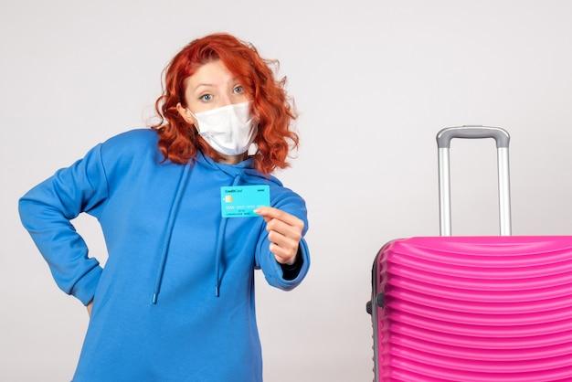 Turista de frente com máscara segurando o cartão do banco