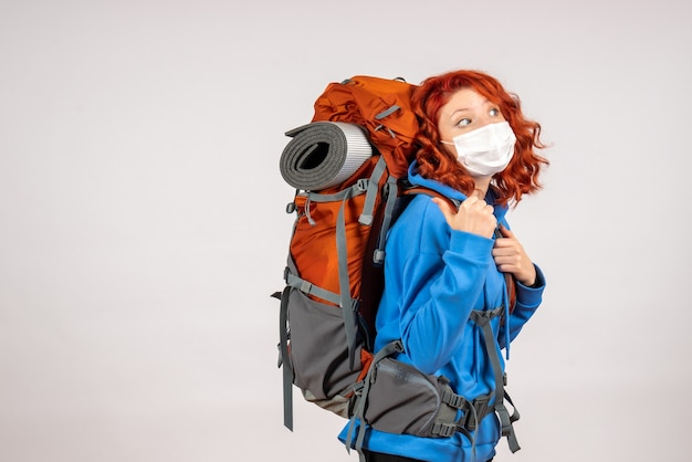 Turista de frente para uma viagem na montanha com máscara e mochila