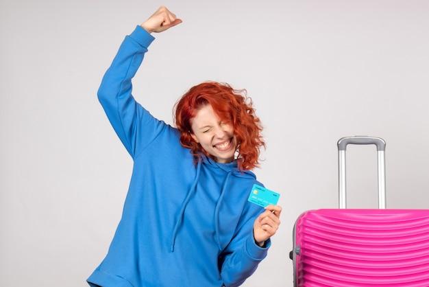 Turista de frente segurando um cartão do banco e se alegrando