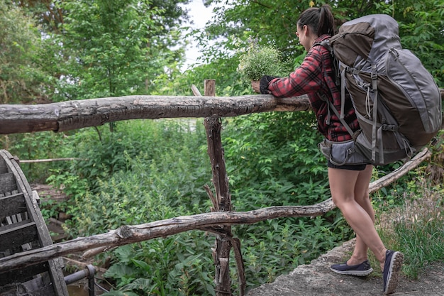 Turista de garota atraente com uma mochila grande para viajar e com um buquê de flores silvestres.