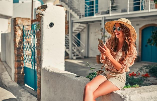 Turista de garota atraente em óculos de sol, blusa e chapéu de palha usa um smartphone por casa da cidade. o conceito de turismo, viagens, lazer.