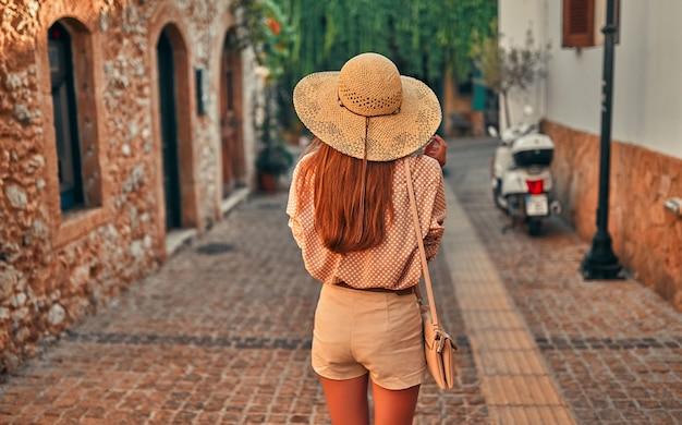 Turista de garota atraente em óculos de sol, uma blusa e um chapéu de palha está caminhando pelos becos da cidade. o conceito de turismo, viagens, lazer.