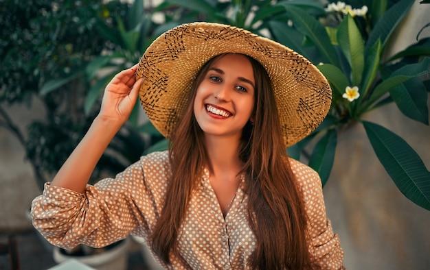 Turista de garota atraente em uma blusa e um chapéu de palha por flores exóticas. o conceito de turismo, viagens, lazer.