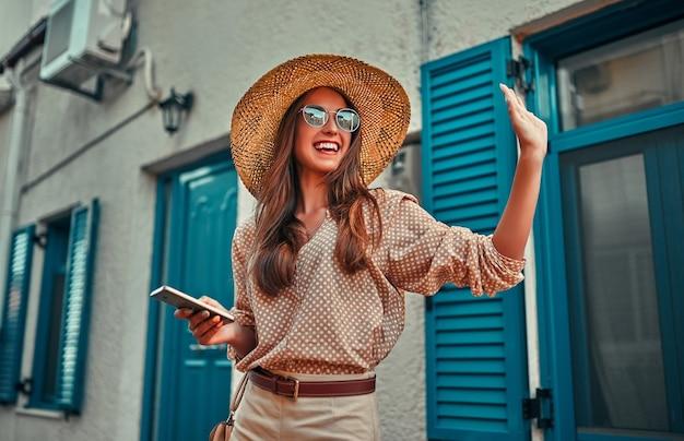 Turista de garota atraente em uma blusa, óculos escuros e chapéu de palha usa um smartphone por uma casa com persianas azuis e acena para alguém. o conceito de turismo, viagens, lazer.