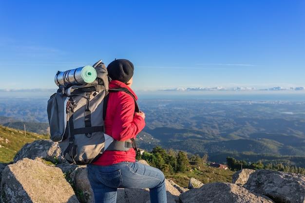 Turista de garota com uma mochila no topo de uma montanha. em uma campanha em portugal.