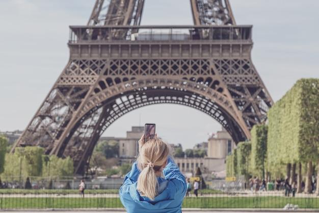 Turista de garota tirando fotos da torre eiffel.