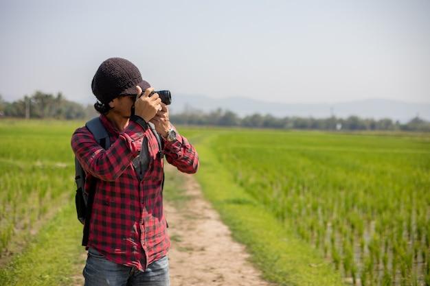Turista de homem asiático está usando uma câmera para tirar fotos de paisagens e montanhas. tempo relaxado em viagens de conceito de férias