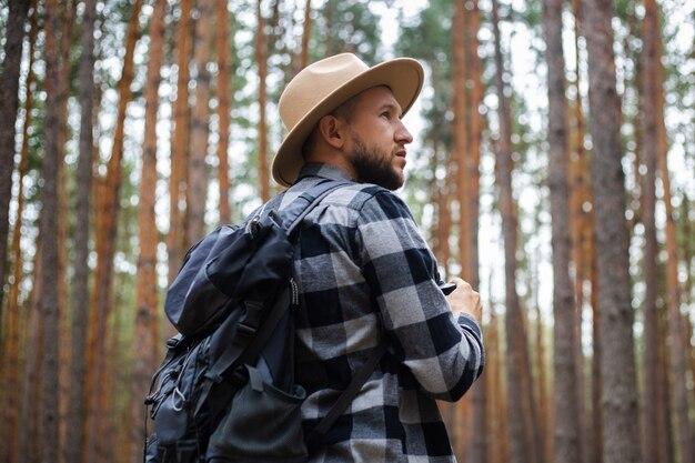 Turista de homem com binóculos durante uma caminhada na floresta. faça caminhadas nas montanhas ou na floresta.