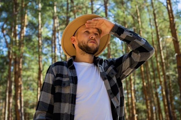 Turista de homem com chapéu e camisa xadrez na floresta.