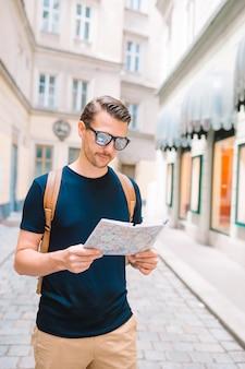 Turista de homem com um mapa da cidade e mochila nas ruas da europa.