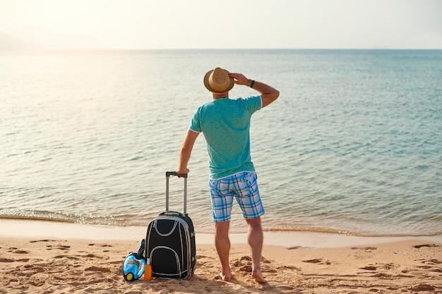 Turista de homem em roupas de verão com uma mala na mão, olhando para o mar na praia
