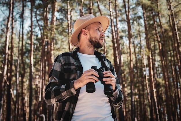 Turista de homem em um chapéu e uma camisa xadrez cinza parece através de binóculos.
