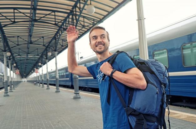 Turista de homem feliz com mochila fica na plataforma da estação ferroviária, cumprimentando amigos ou dizendo adeus, acenando a mão. viajar de trem.