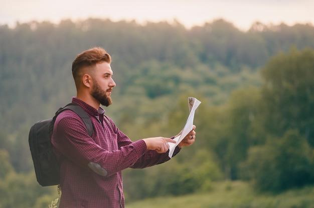 Turista de homem na montanha, leia o mapa.