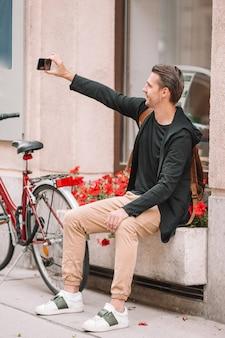 Turista de homem na rua europa. menino caucasiano olhando com o mapa da cidade europeia.
