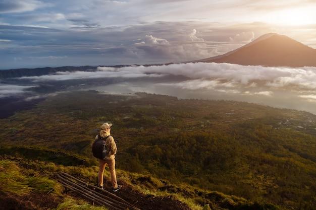 Turista de homem olha para o nascer do sol no vulcão batur, na ilha de blai, na indonésia. homem alpinista com mochila viajar no topo do vulcão, conceito de viagens