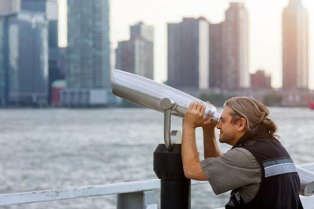 Turista de homem olhando através de binóculos. no topo de nova york, a torre da liberdade