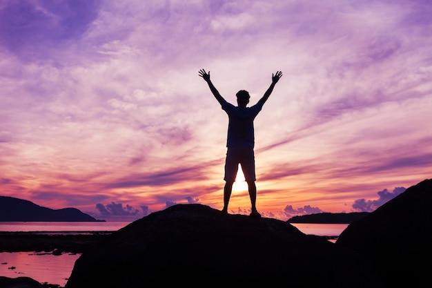 Turista de homem sozinho em pé sobre a pedra no mar tropical e apreciando a paisagem durante sunris