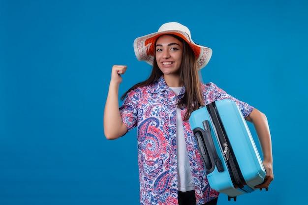 Turista de jovem mulher bonita no chapéu do verão com mala de viagem positivo e feliz levantando o punho após uma vitória, sorrindo alegremente, pronto para viajar sobre bl isolado