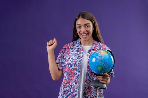 Turista de jovem mulher bonita segurando o globo, levantando o punho após a vitória com cara feliz sorrindo alegremente sobre parede roxa