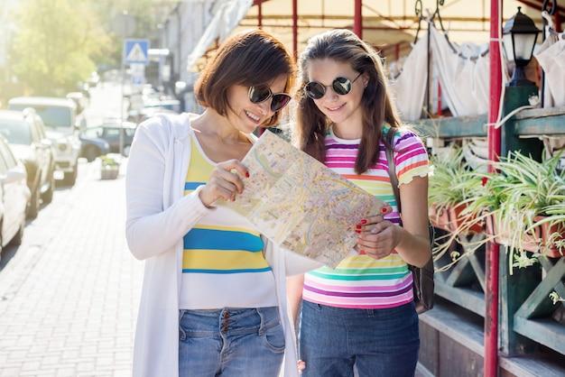 Turista de mãe e filha adolescente olhando para o mapa