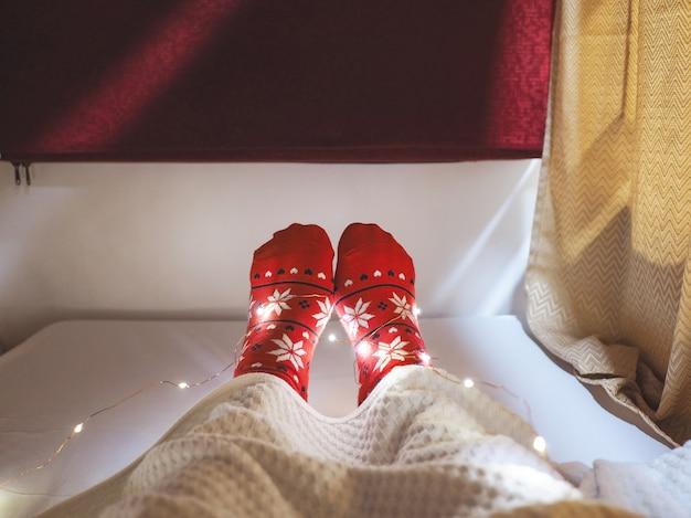 Turista de meias vermelhas com pés de selfie de padrão de natal na cama na cápsula do hotel.