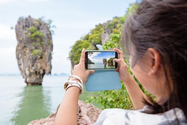 Turista de menina adolescente tirando foto de marco de uma bela paisagem em vista panorâmica por telefone celular em koh tapu ou na ilha james bond no parque nacional da baía de ao phang nga, mulher viajando natureza ásia na tailândia