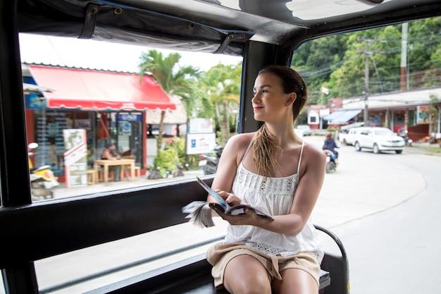 Turista de menina em um táxi tailandês tuk tuk