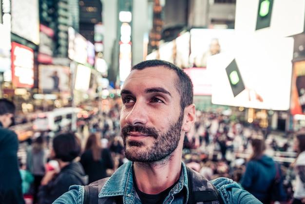 Turista de mochileiro tomando selfie na time square, nova iorque