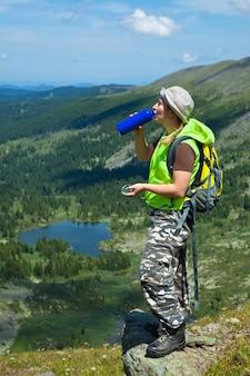 Turista de montanhas bebendo água da garrafa
