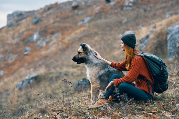 Turista de mulher alegre ao lado de uma paisagem de montanhas de amizade de cachorro. foto de alta qualidade