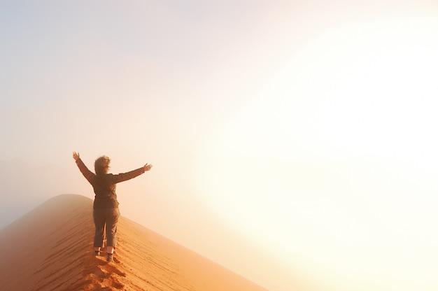 Turista de mulher andando em cima de dunas no deserto do namibe, viagens de férias na áfrica, aventura na namíbia