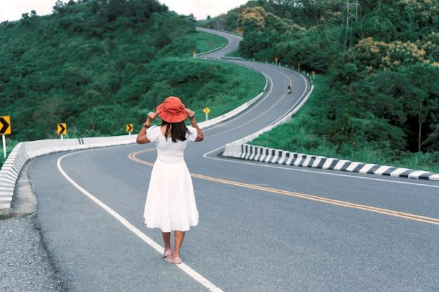 Turista de mulher asiática andando na estrada curva entre a montanha verde. 3 estrada curva, atração da viagem em nan, tailândia.