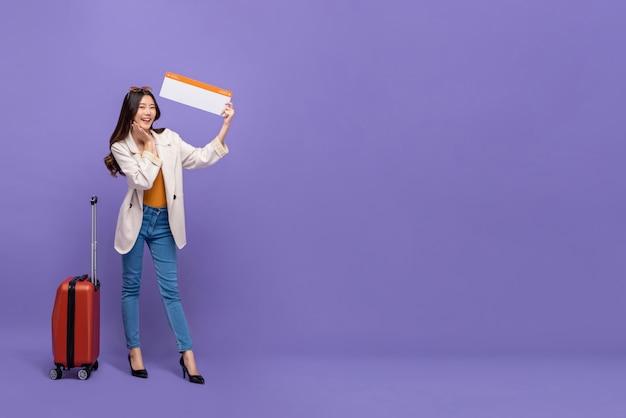 Turista de mulher asiática com bagagem mostrando o cartão de embarque confirmado