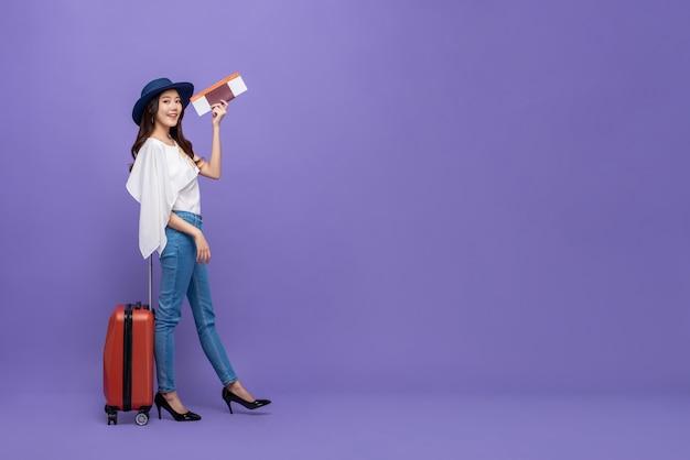 Turista de mulher asiática com bagagem mostrando o passaporte e cartão de embarque