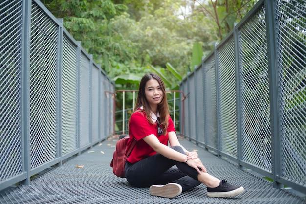 Turista de mulher asiática com mochila vermelha e óculos de sol sentado na passarela de ferro